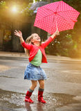 Child with polka dots umbrella wearing red rain boots. Jumping into a puddle Royalty Free Stock Photography