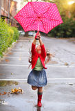 Child with polka dots umbrella wearing red rain boots. Jumping into a puddle stock photos
