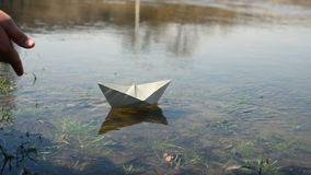 Child at the pond with a paper boat. A child starts up a paper boat. Close-up the hand and the paper boat stock video