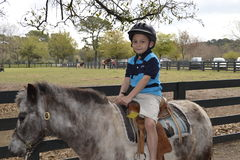 Child with pony. A young boy riding a pony. Lawton Stables on Hilton Head Islannd, SC Stock Photo