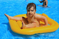 Child in the pool. Baby floating in the pool Royalty Free Stock Photography