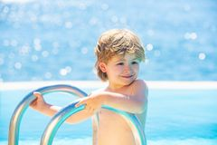 Child in the pool. Happy boy goes down to the pool. Swimming lessons. Smiling cute little kid in pool in sunny day. royalty free stock images