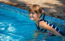 Child in the pool. Little girl with a mischievous smile in the pool Royalty Free Stock Photo