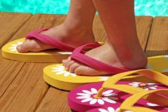 Child by pool wearing flipflops. Child trying on flipflops on deck next to pool royalty free stock images
