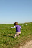 Child pooling line. Young girl pooling fence line in a countryside Royalty Free Stock Photography