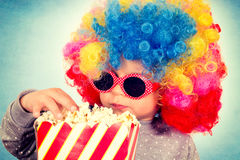 Child and pop corns. Little child with clown wig and retro sunglasses eating pop corn Royalty Free Stock Images