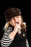 Child Pop Star. A young girl is singing like a pop star, isolated against a black background Royalty Free Stock Photos