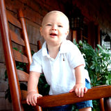 Child on Porch. Child on rocking chair on front porch of family home Royalty Free Stock Photo