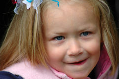 Child portrait. A young happy beautiful little shy girl toddler portrait with shy expression and blue eyes Royalty Free Stock Photos