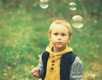 Child portrait with soap bubbles in park Royalty Free Stock Photo