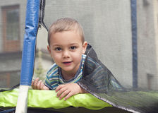 Child portrait on a trampoline. Portrait of a child peeking from a trampoline through the door in safety net Stock Photo