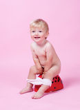 Child on the pot. Little girl on the pot royalty free stock images