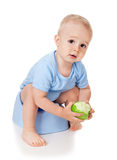 The child on a pot with an apple Royalty Free Stock Image