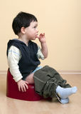 Child on potty. A cute toddler child boy sitting on a red potty royalty free stock image