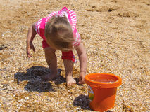 Child pours sand into the bucket. The child pours sand into the bucket royalty free stock photography