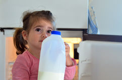 Child Poverty. Hungry poor little girl holds a bottle of milk at home royalty free stock images