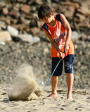 Child practice golf at the beach. A 10 years old boy enjoys hitting the golf club  at the beach Royalty Free Stock Photos
