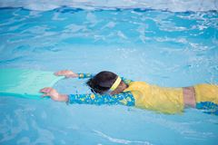 Child practice swimming by floating foam. Child or boy practice to swim in swimming pool with floating foam stock photos
