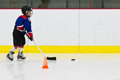 Child practices stickhandling at ice hockey practice Stock Images