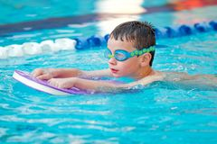 Boy Practice Swimming. Child is practicing swim in pool with googles Royalty Free Stock Photo