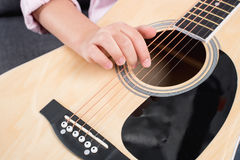 Child practicing to play on acoustic guitar Royalty Free Stock Images