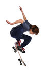 Child practicing a trick on skateboard. Isolated on a white background Stock Photography