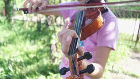 Child practicing the violin. Outdoor stock video footage