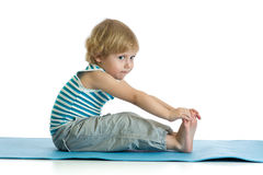 Child practicing yoga, stretching in exercise wearing sportswear. Kid isolated over white background Royalty Free Stock Image
