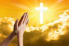 Child Prayer Hands Praying Faith. A young girls hands praying with a cross in a sky background Stock Photo