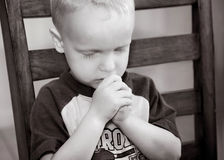 Child Praying. Young child praying before his meal.  The little boy is sitting in his chair at the dinner table, head bowed and hands together in prayer Royalty Free Stock Photography