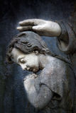 Child Praying. With an adult hand hovering above his head from a monument in the Churchyard of St Cuthbert's in Edinburgh, Scotland Stock Photo