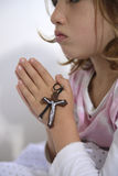 Child praying with cross Stock Photos