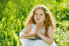 Child with praying or dreaming  in the park outdoors. Stock Photo