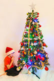 Child praying in front of a Chrismas Tree royalty free stock photo
