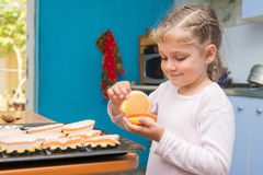 The child is prepared for feast of Easter, laying on a baking tins Easter cupcakes Stock Photography