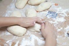 Child prepares the dough of flour for pasta pastry bread. Chef child prepares the dough of flour for pasta pastry pizza bread, flour your hands Royalty Free Stock Photos