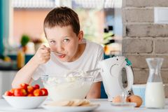 Child preparing cake and tasting dough in domestic kitchen Royalty Free Stock Photos