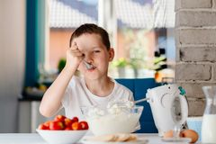 Child preparing cake and tasting dough in domestic kitchen Royalty Free Stock Photography