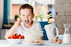 Child preparing cake and tasting dough in domestic kitchen Stock Image