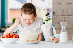 Child preparing cake and tasting dough in domestic kitchen Royalty Free Stock Photo