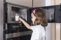 Child preparing a glass of milk Royalty Free Stock Photos