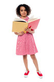 Child preparing for her examinations. School girl in uniform reading a textbook stock image
