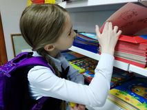 Child is preparing for school. The child chooses the store school supplies. Preparation for school stock image