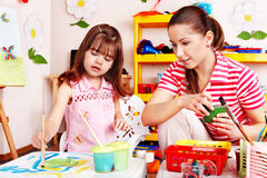 Child in preschool with teacher draw. stock image