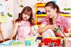 Child in preschool with teacher draw. Child preschooler with teacher draw paint in play room. Preschool stock image