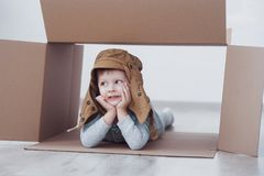 Child preschooler boy playing inside paper box. Childhood, repairs and new house concept.  Royalty Free Stock Image