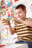 Child  preschooler painting in classroom. Stock Photos