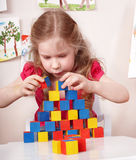 Child preschooler play wood block in play room. Stock Image