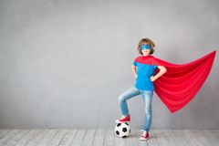 Child pretend to be soccer superhero. Kid playing with ball at home. Success, win and imagination concept Stock Image