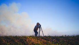 Child pretending to be a photographer. A toddler girl holding a toy looking into a camera tripod with a cloud of smoke behind her and autumn leaves and grass in Stock Photos